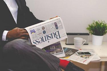 Man som läser tidning med affärsnyheter