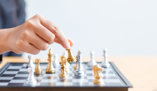 Guld-silver pjäser på schackbräde