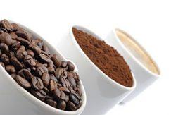 Kaffebönor, kaffepulver och en kaffekopp