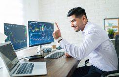 Professionell valutahandlare med 3 skärmar