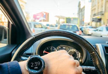 Tittar på klockan medan han kör