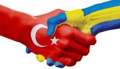 Turk- och svenskmålade händer skakar hand